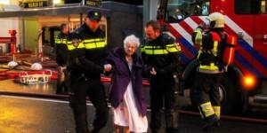 en oudere bewoonster wordt in veiligheid gebracht nadat het Nijmeegse complex waarin ze woont, door brand is getroffen.